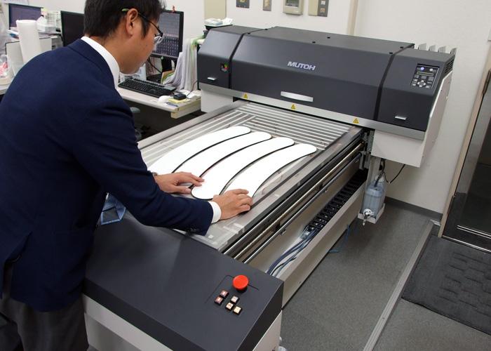 ※アーチ状のパネルを印刷機に並べる河波様。